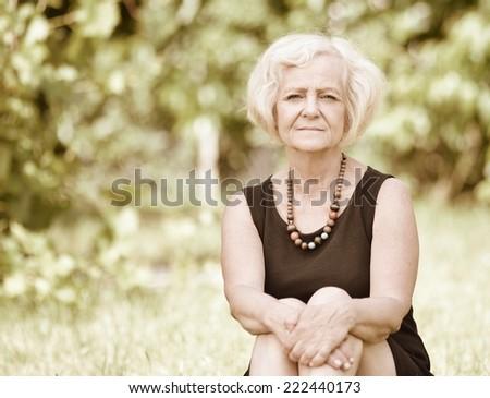 Mature, blonde woman in garden, Vintage style. - stock photo