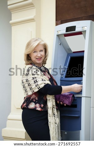 Mature blonde woman with credit card in hand near automated teller machine in shop - stock photo
