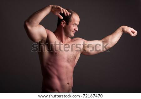 mature bodybuilder posing in studio - stock photo
