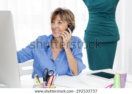 Mature brown haired  fashion woman  designer sitting at the desk talking by phone and looking at a computer monitor. - stock photo
