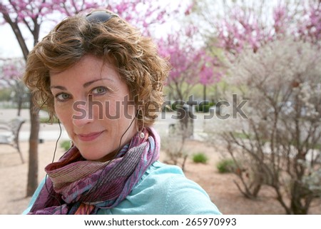 Mature brunette woman relaxing outside with beautiful spring red buds flowers blooming - stock photo