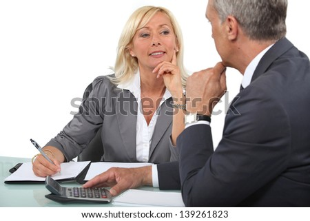 Mature business couple at a desk with a calculator - stock photo