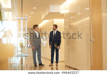 Mature business executive standing in a modern office building foyer, talking with a stylish young employee - stock photo