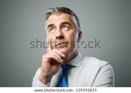 Mature business man looking up and thinking about something - stock photo