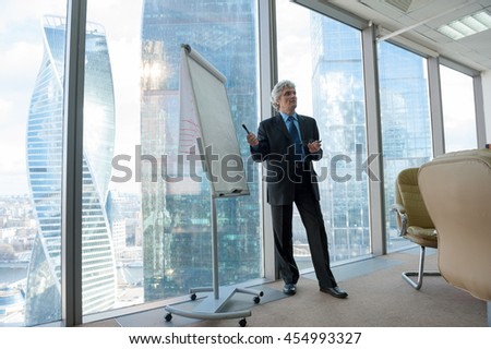 Mature business man making a presentation in modern office - stock photo