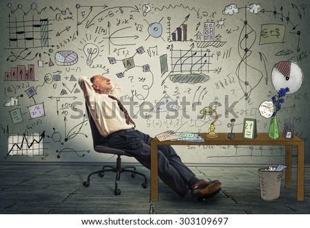 Mature business man relaxing at his desk in his office  - stock photo