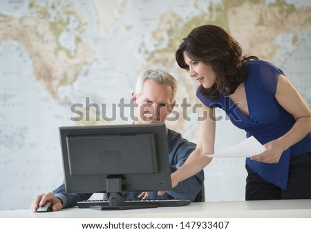 Mature business people working on computer at office desk with world map in background - stock photo