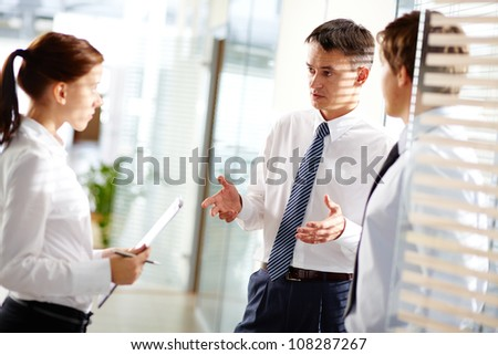 Mature businessman addressing his young secretary while discussing business matters - stock photo
