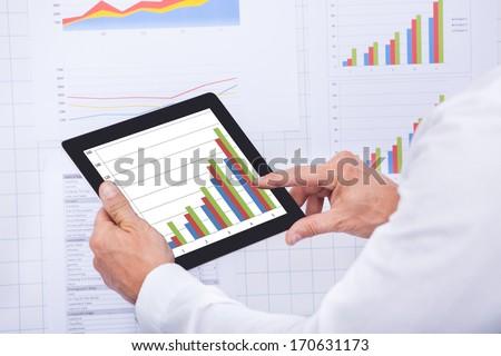 Mature Businessman Analyzing Graph On Digital Tablet - stock photo