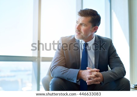 Mature businessman and corporate entrepreneur sitting in a modern office space with large windows, looking away with a positive and optimistic expression - stock photo
