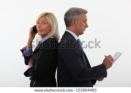 mature businessman and female partner standing back to back - stock photo