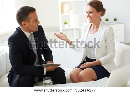Mature businessman and his colleague discussing working plans in office - stock photo