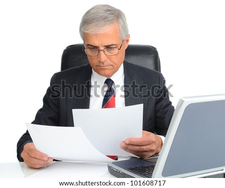 Mature businessman at desk reading papers. Man is wearing eye glasses and has a laptop computer. - stock photo