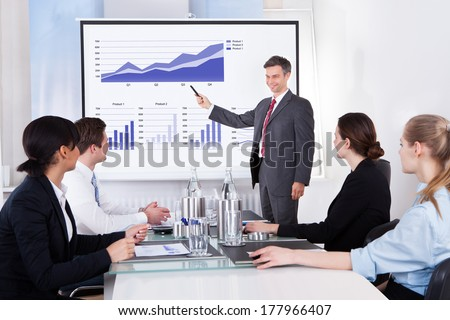Mature Businessman Explaining Graph To His Colleagues Sitting In Office - stock photo