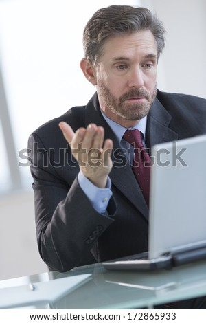Mature businessman gesturing while using laptop at desk in office - stock photo
