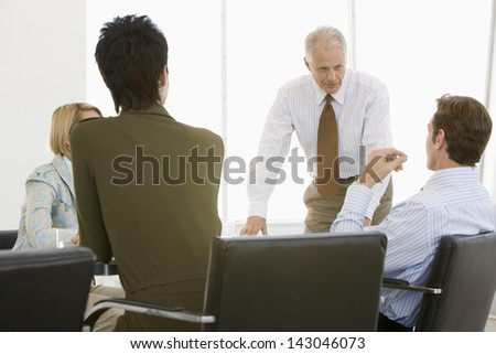 Mature businessman having discussion with team in conference room - stock photo