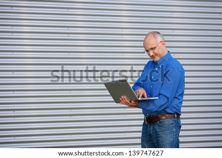 Mature businessman holding laptop while looking away, outdoor - stock photo