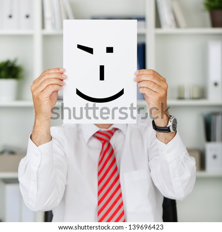 Mature businessman holding wink smiley in front of his face at office - stock photo