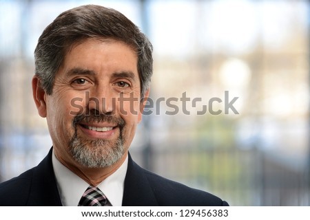 Mature businessman in his office with building on the background - stock photo
