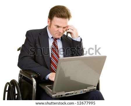 Mature businessman in wheelchair using his laptop and talking on the phone.  Isolated on white. - stock photo
