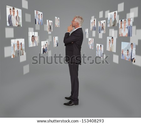Mature businessman looking at digital interface showing partners - stock photo