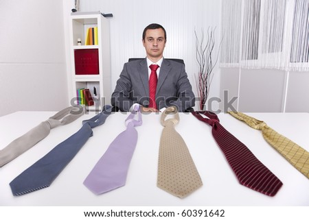 mature businessman looking to a lot of neckties, thinking what to choose - stock photo
