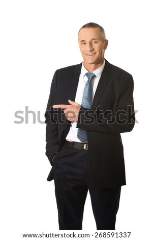 Mature businessman pointing to the left. - stock photo