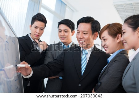 Mature businessman presenting new strategy to his young colleagues - stock photo