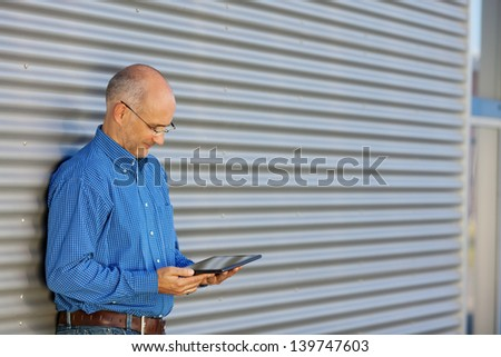 Mature businessman reading on digital tablet against shutter - stock photo