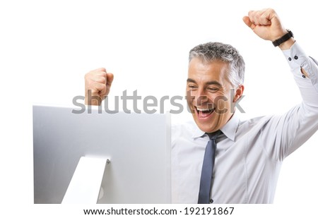 Mature businessman receiving good news on computer with fists raised. - stock photo
