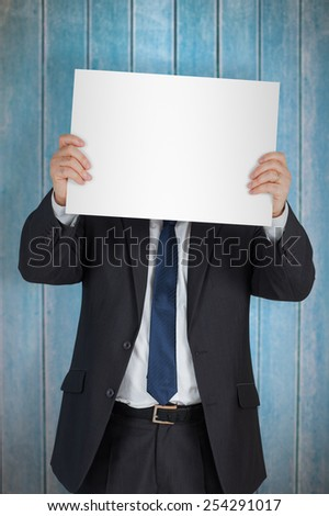 Mature businessman showing card against wooden planks - stock photo