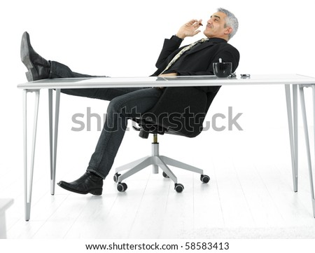 Mature businessman sitting at desk in confident pose, smoking cigar. Isolated on white. - stock photo