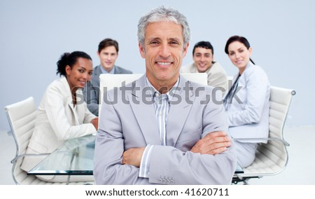Mature businessman smiling in a meeting with his team working in the background - stock photo