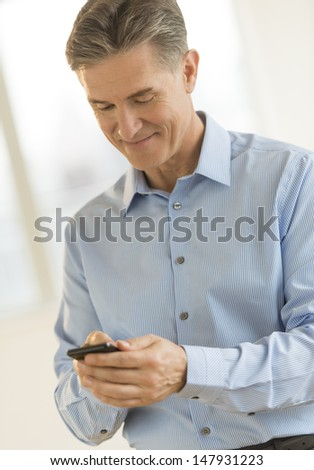 Mature businessman smiling while text messaging through smart phone in office - stock photo