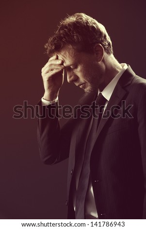Mature businessman stressed and worried looking down - stock photo