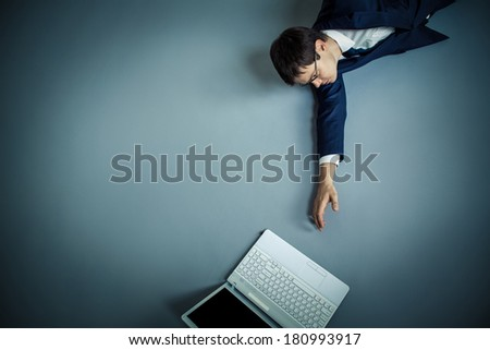 Mature businessman stretches to laptop - stock photo