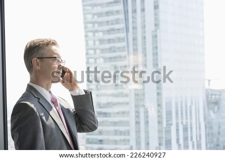 Mature businessman talking on cell phone by window - stock photo