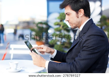 Mature businessman using a tablet outdoor - stock photo