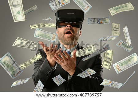 MAture businessman using virtual reality glasses getting money into hands - stock photo