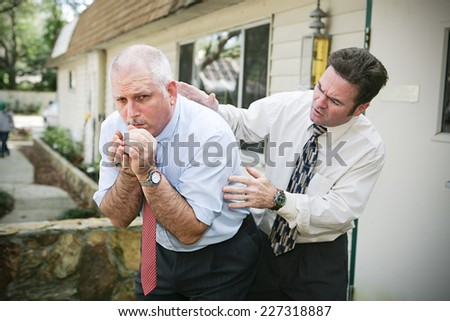 Mature businessman with a bad cough.  His friend and colleague is worried about him and pats him on the back trying to help.  Vignette added. - stock photo