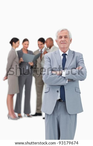 Mature businessman with arms folded and team behind him against a white background - stock photo