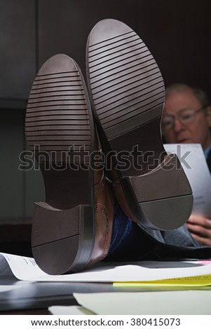 Mature businessman with his feet up on the desk - stock photo