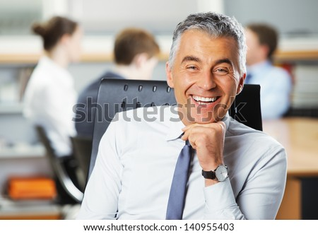 Mature businessman with meeting in the background - stock photo