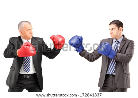 Mature businessman with red boxing gloves ready to fight his coworker isolated on white background - stock photo