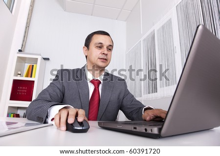 Mature businessman working at the office with his laptop - stock photo