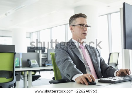 Mature businessman working on computer in office - stock photo
