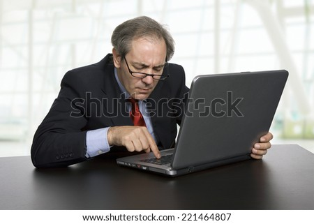 mature businessman working with his laptop at the office - stock photo