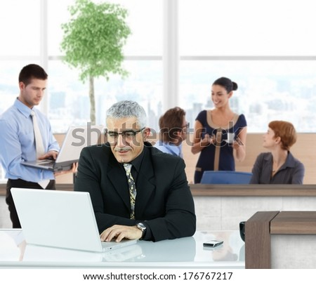 Mature businessman working with laptop in office hallway. - stock photo