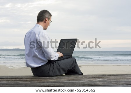 Mature businessman working with laptop on a beach - stock photo
