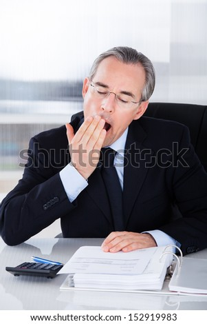Mature Businessman Yawning While Calculating At Desk - stock photo